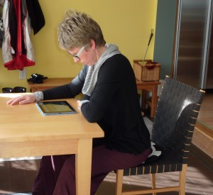 looking down at an i-pad flat on the table with head hanging forward of the body