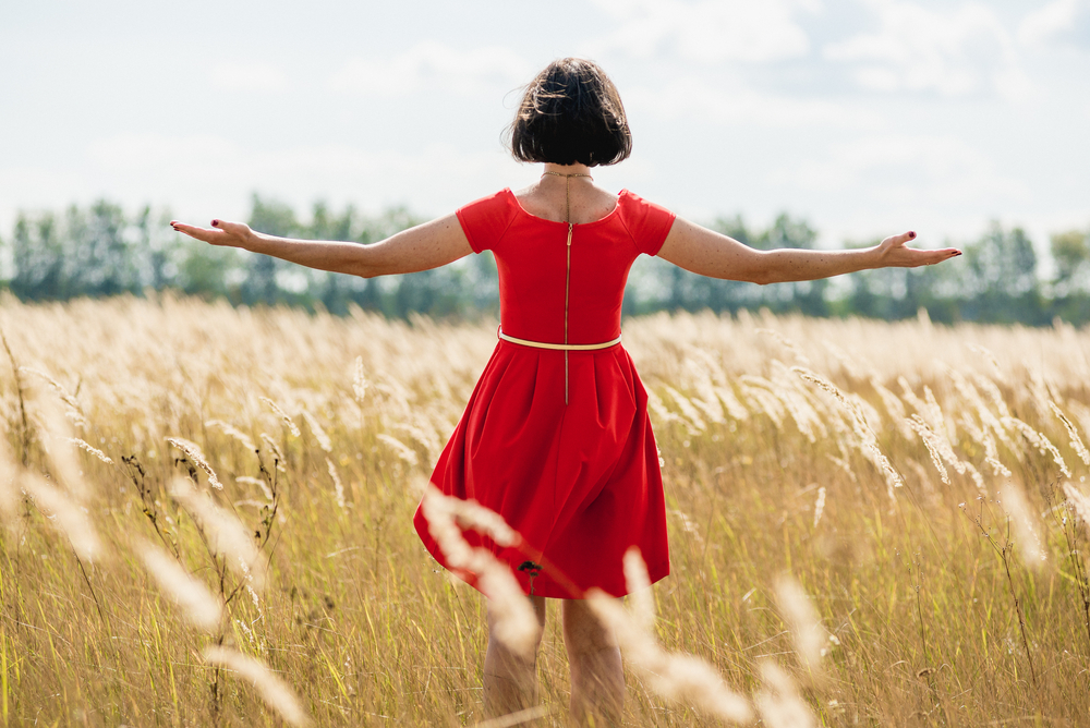 woman standing in meadow with outstretched arms