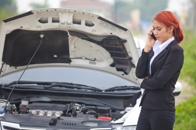 woman standing next to broken down car