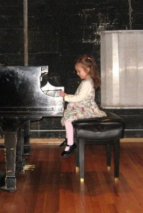 little girl sitting playing the piano