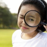 young child looking through a magnifying glass