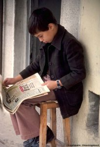 boy leaning over reading a newspaper on his lap