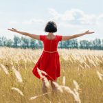 woman in red dress standing in meadow with arms outstretched