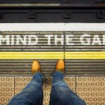 person standing on train platform with words mind the gap