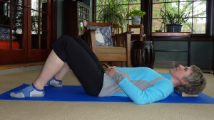 Demonstration of the Constructive Rest position with legs bent and feet flat on the floor