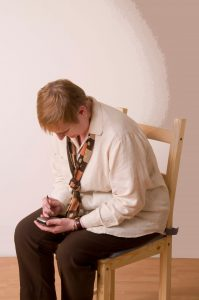 woman seated bent over texting
