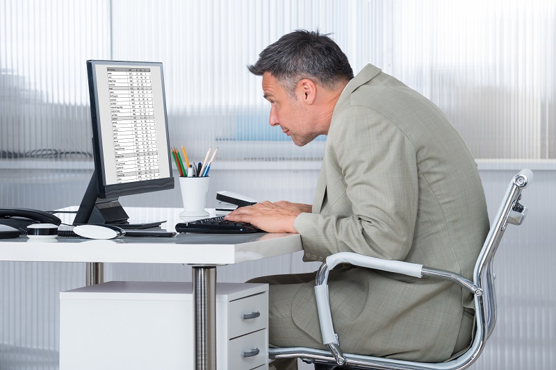 man rounded forward and working at computer
