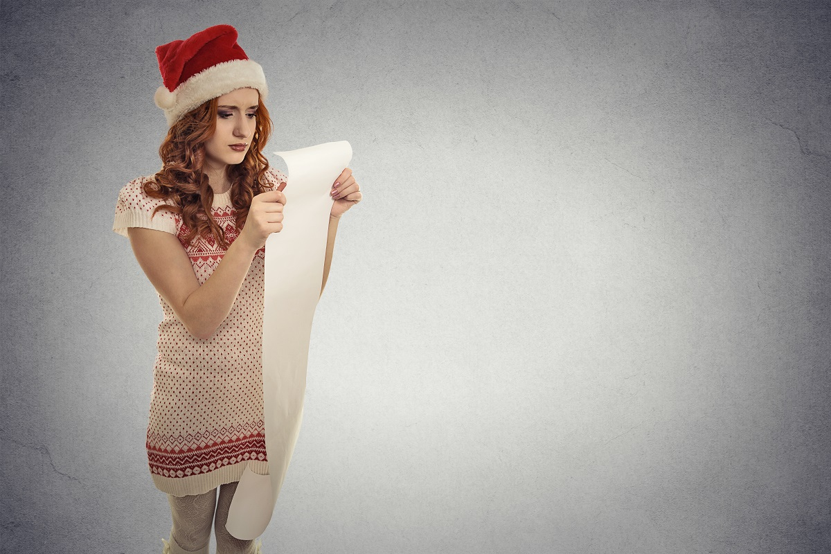 girl with santa hat holding long list