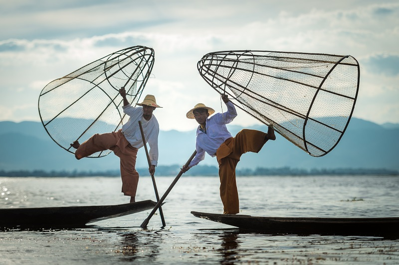 two asian fishermen balancing on their boats