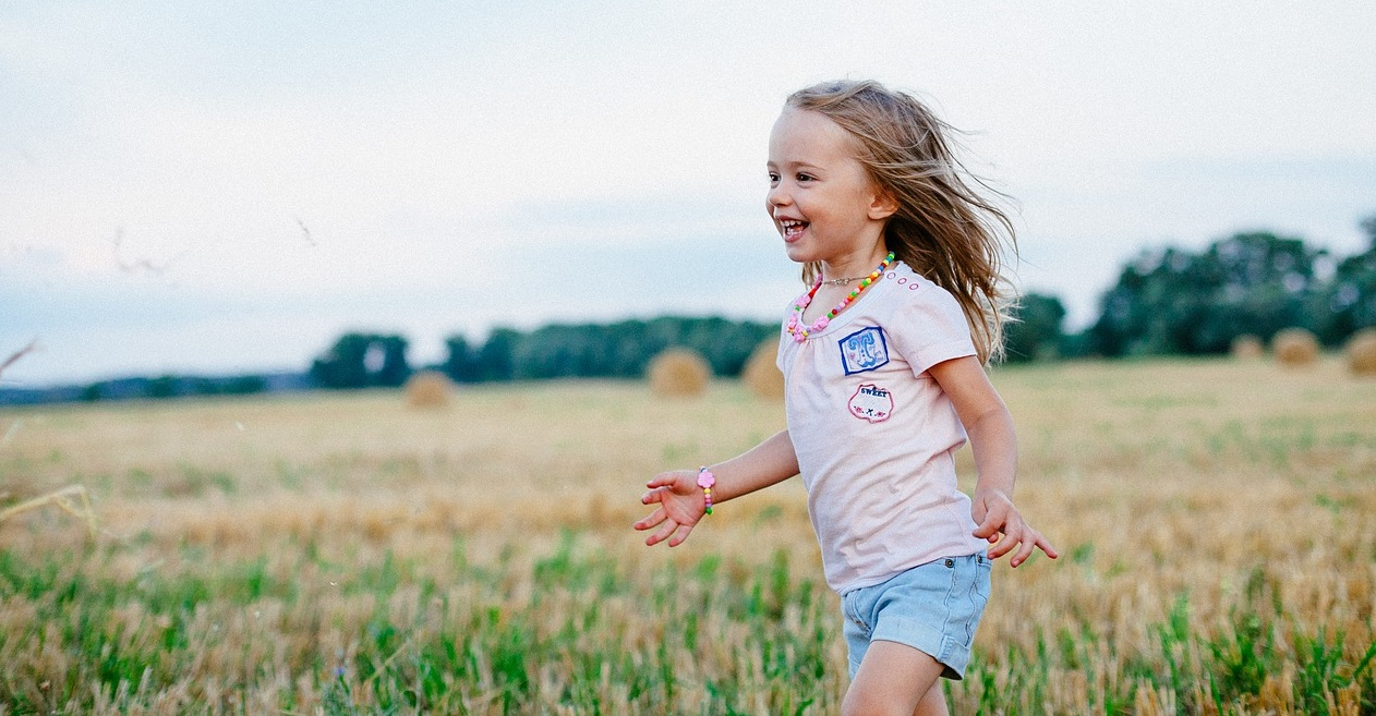little girl joyfully running in field