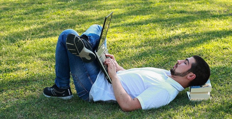 man lying down on the grass outside using laptop