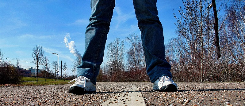 man standing with feet apart on street
